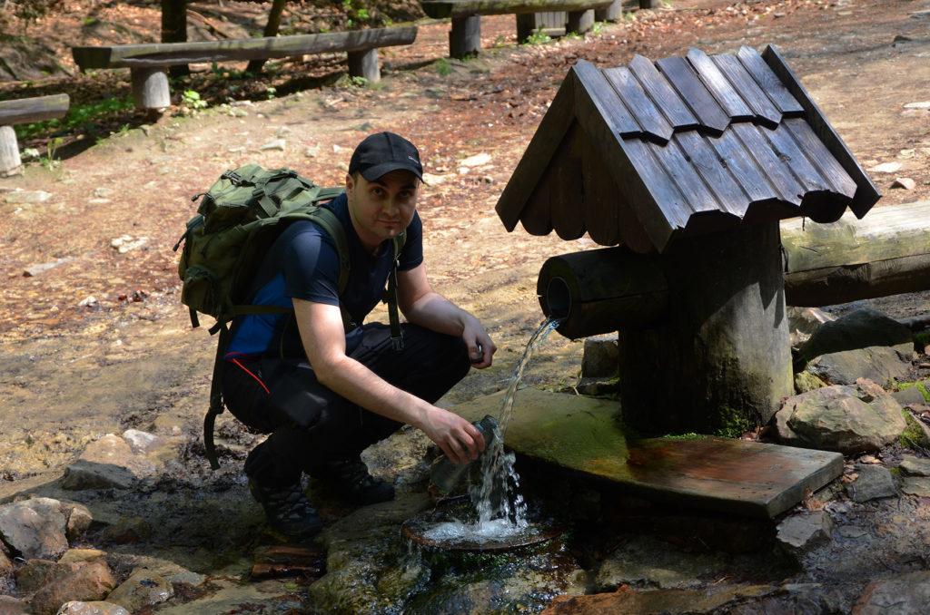 Łukasz napełnia butelkę wodą przy początku szlaku na Łysicę